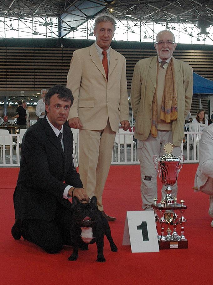 Tre persone con un Bouledogue brindle che ha vinto il primo premio