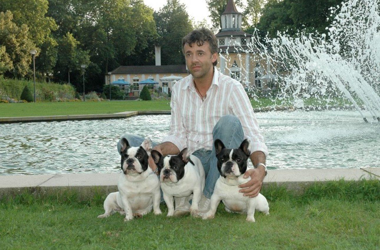 Persona con tre bouledogue pied in un giardino con alle spalle una fontana